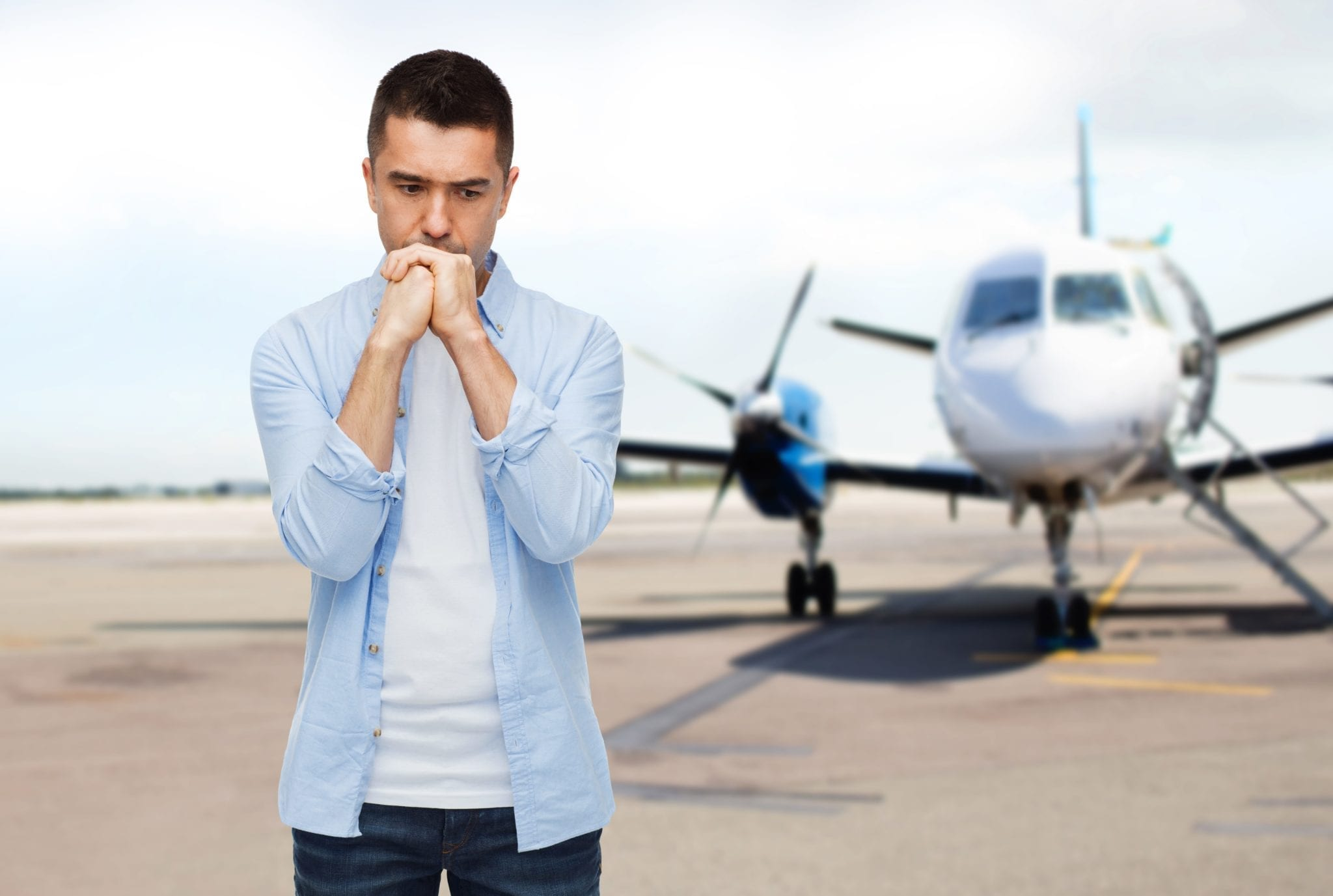 Image of a man in front of a plane looking scared.