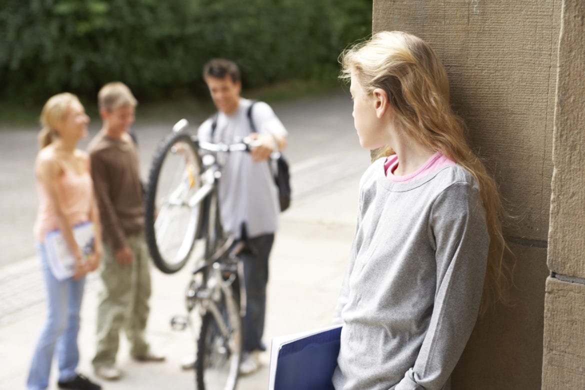 Image of teenage girl leaning against a wall while looking over at three of her classmates hanging out without her.