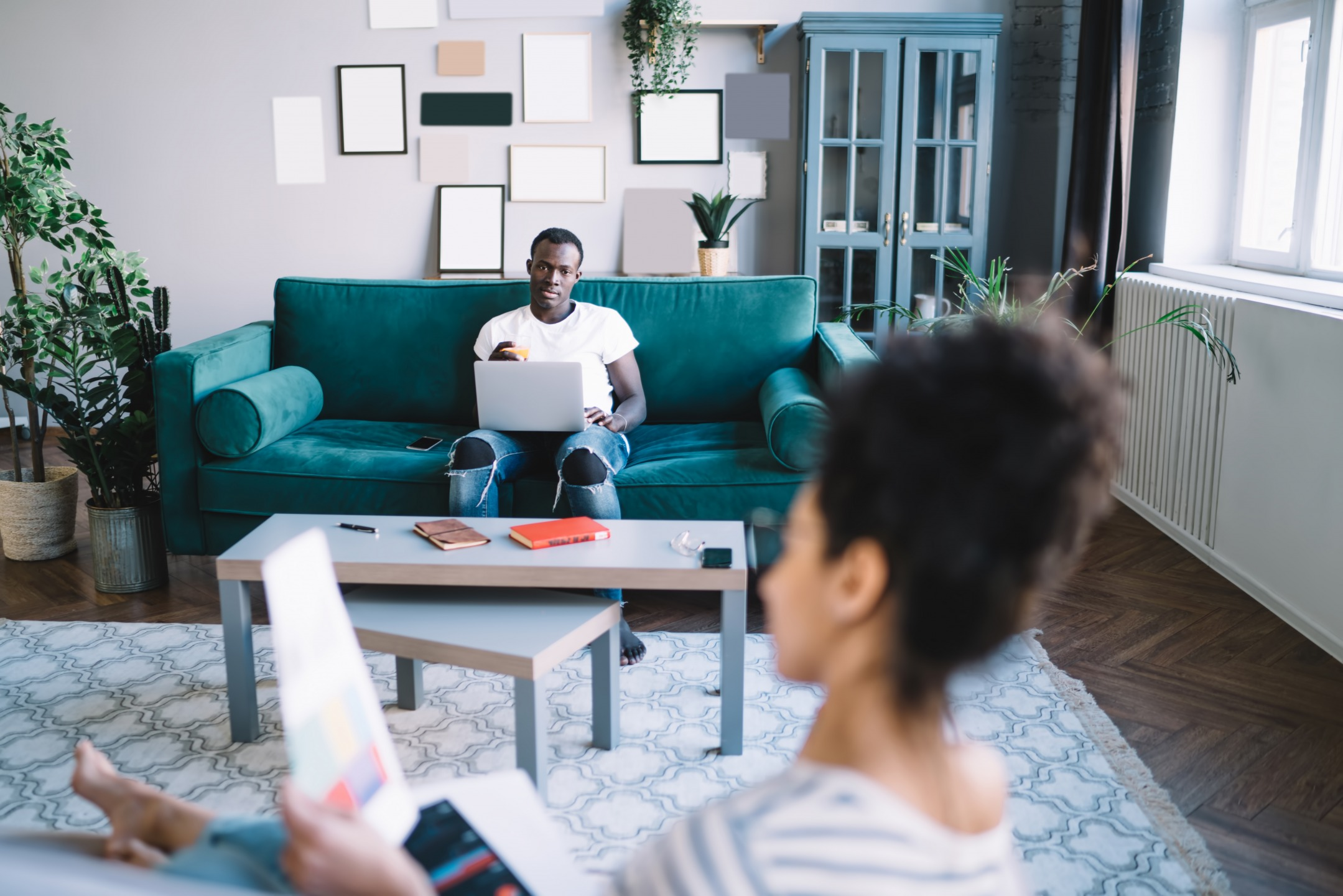 Young Man and Young Woman on Separate Couches Stock Photo