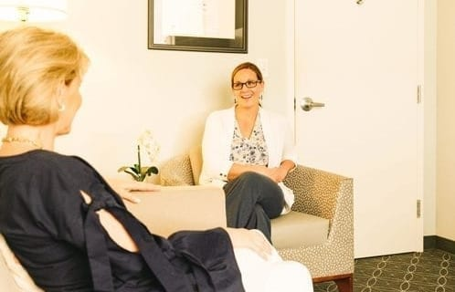 Image of two women sitting in a waiting room having a conversation.