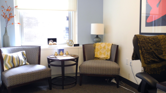 Waiting room with two chairs and table in front of open window.