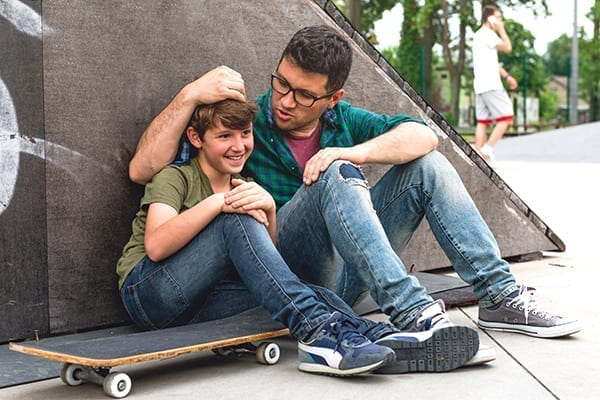 Image of a father and son sitting against a wall with a skateboard near them
