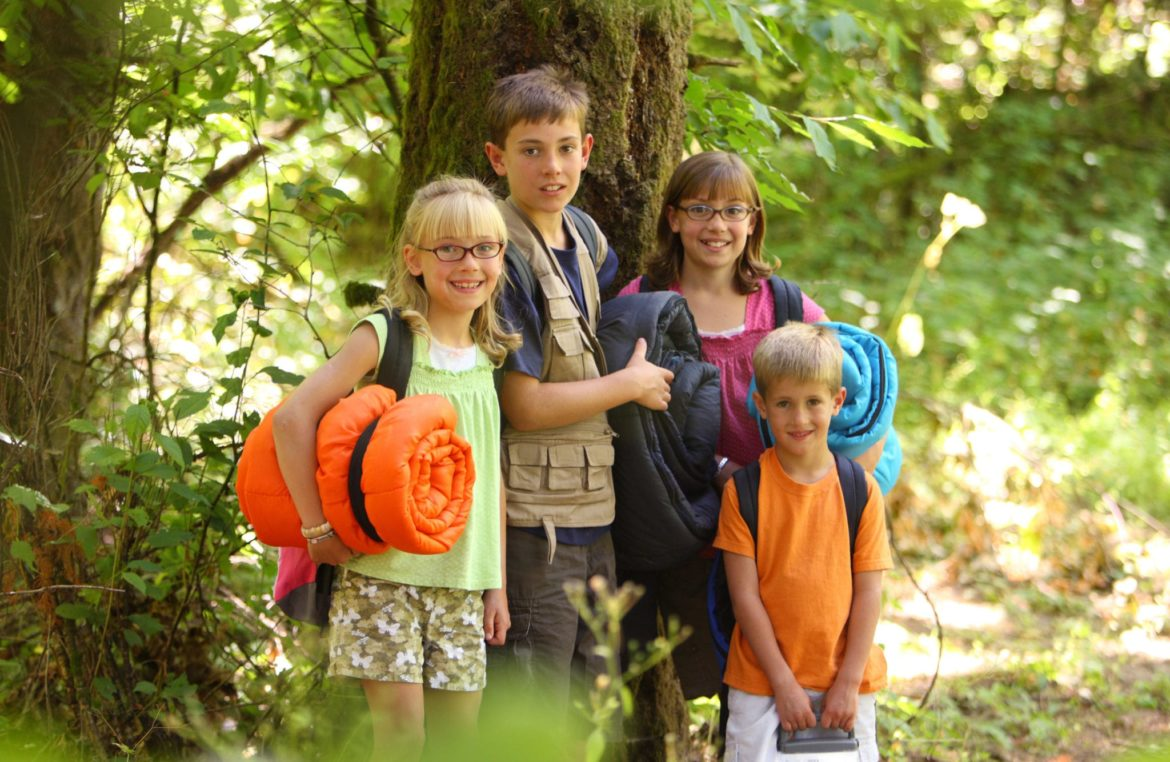 Image of four children in the forest with sleeping bags and camping gear.