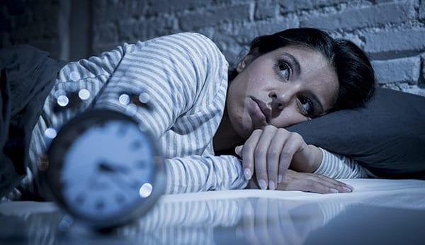 Image of a woman lying in her bed wide awake with an alarm clock in the front of the camera.
