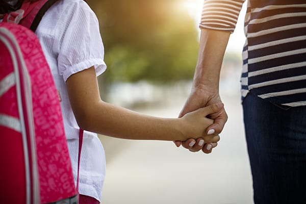 Image of a little girl wearing a backpack and holding her mothers hand.