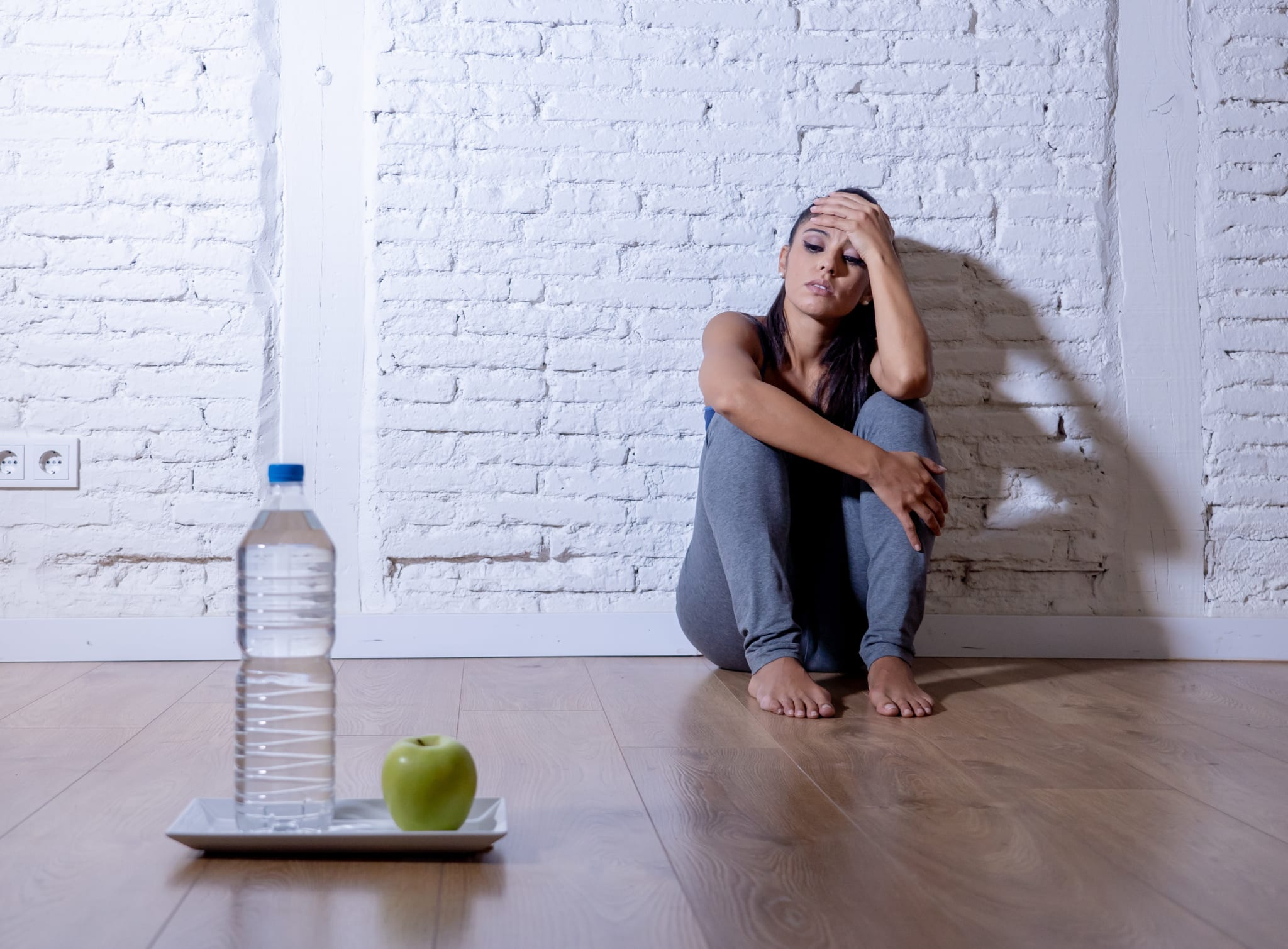 Image of a woman sitting against a wall looking at a water bottle and a green apple.