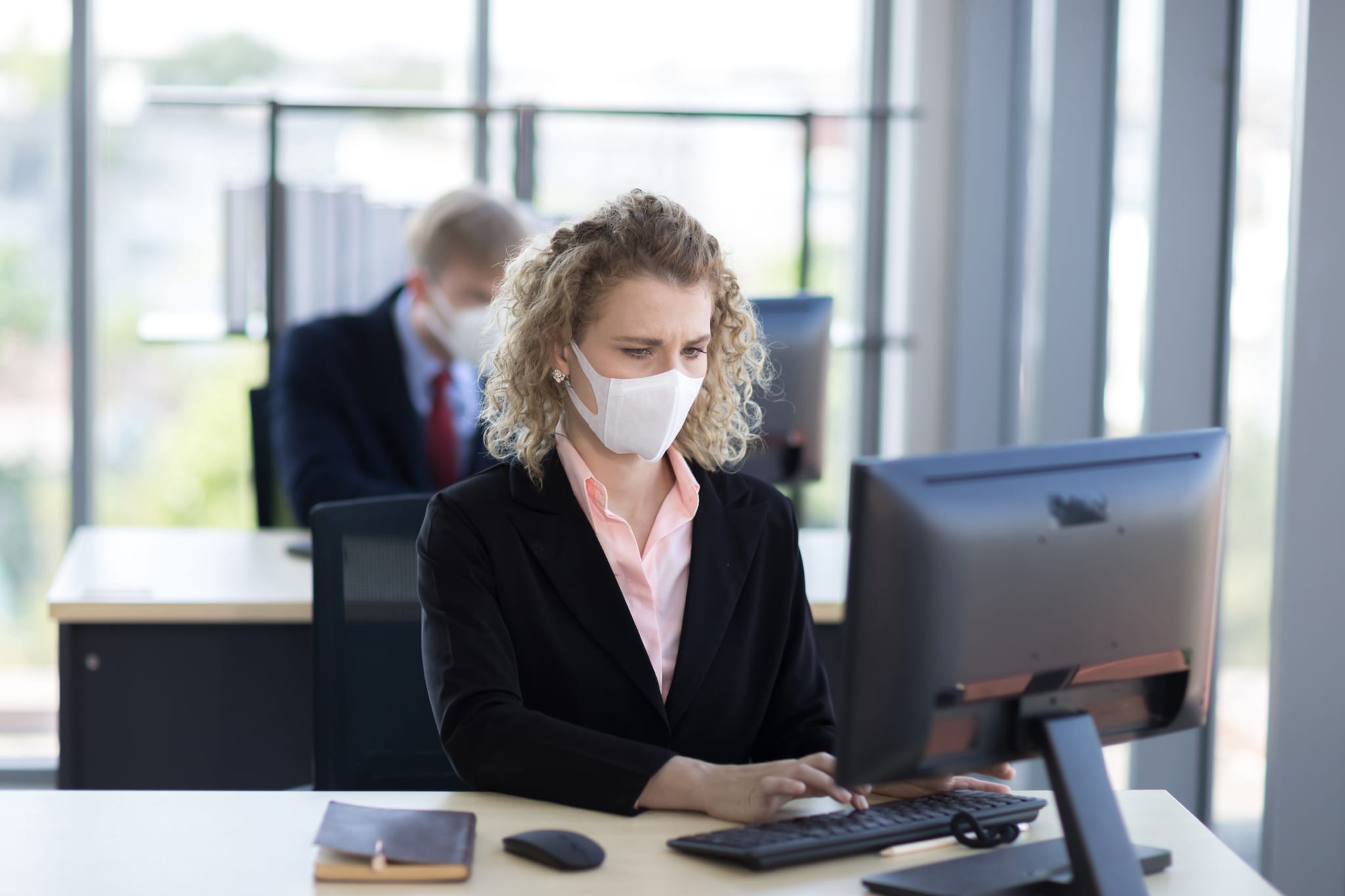 Image of a woman working at her compture with a face mask on.