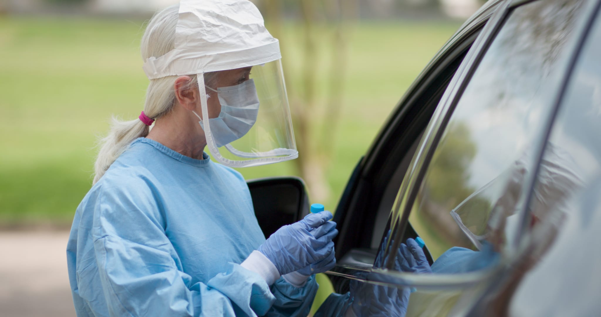 Image of a woman in full PPE testing a person in the car for COVID-19