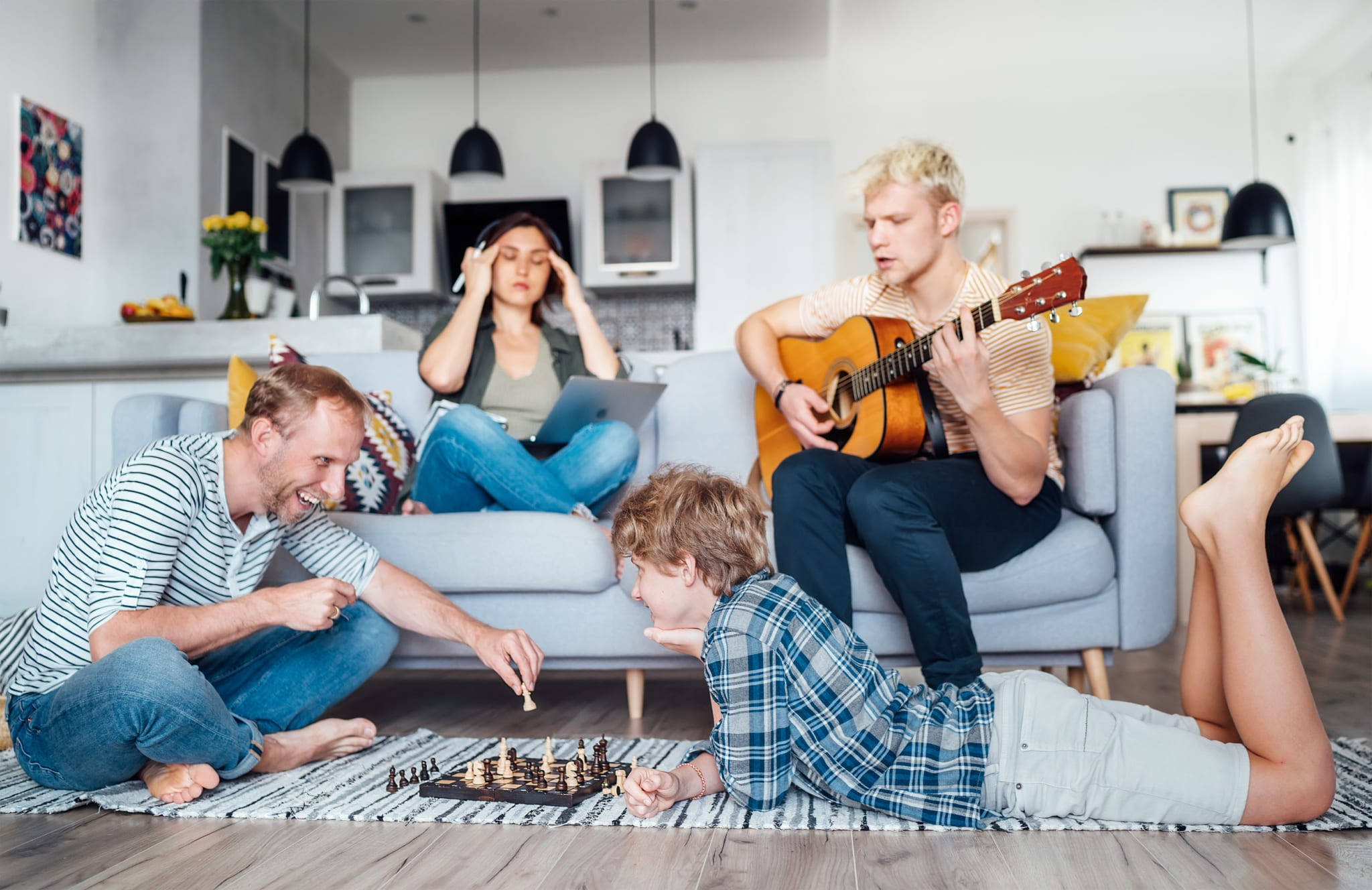 Image of four friends hanging out, one woman is one her laptop, the guy sitting next to her is playing his guitar. The other two friends are laying on the floor playing a game of chess.