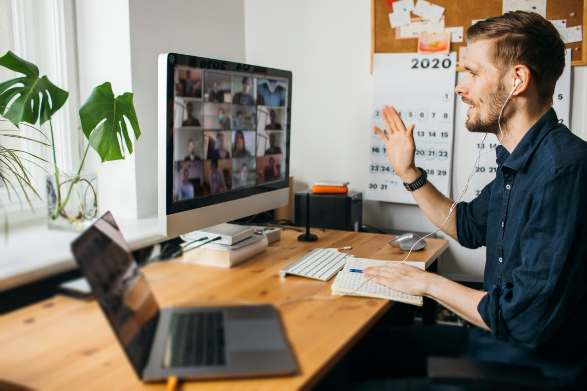 Image of a man sitting at his desktop, while on a video call with 16 people.