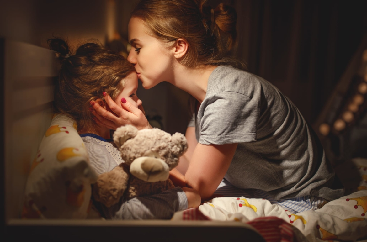 Image of a mother kissing her daughters forehead goodnight.