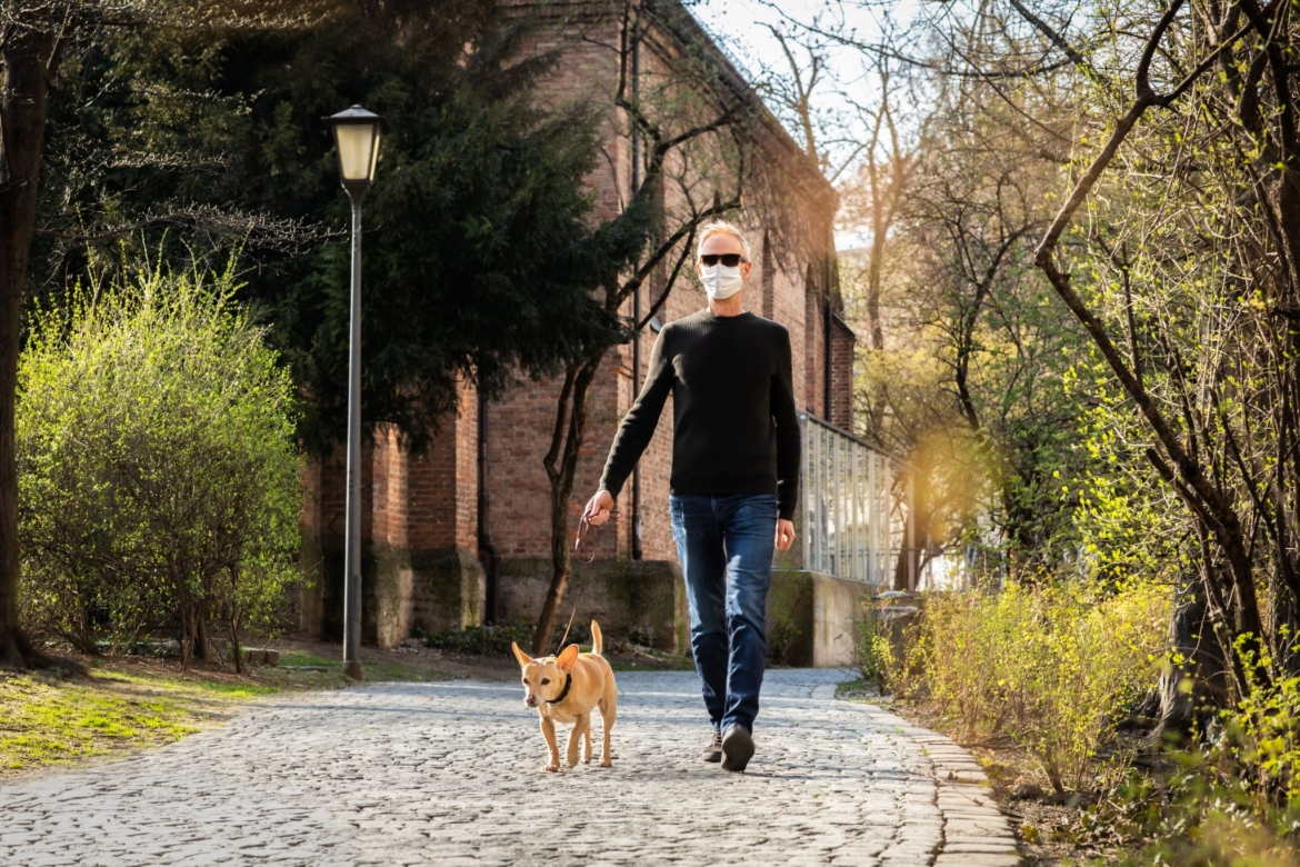 Image of a man wearing a mask while walking his dog outside.