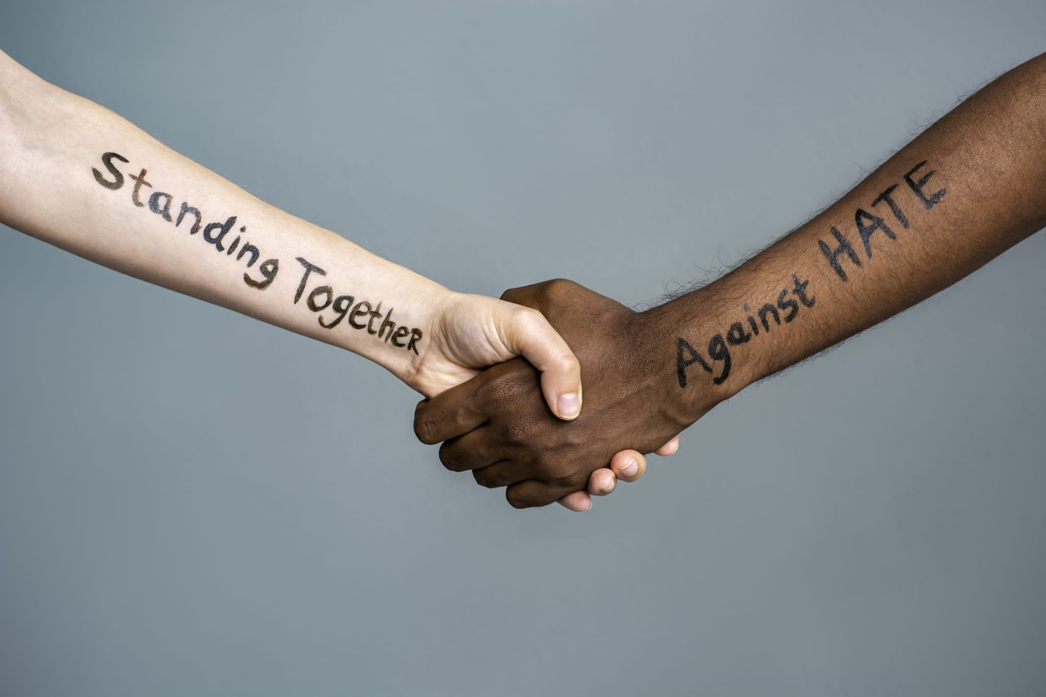 """Image of two people holding hands with the words """"Standing Together Against Hate"""" written on their arms."""