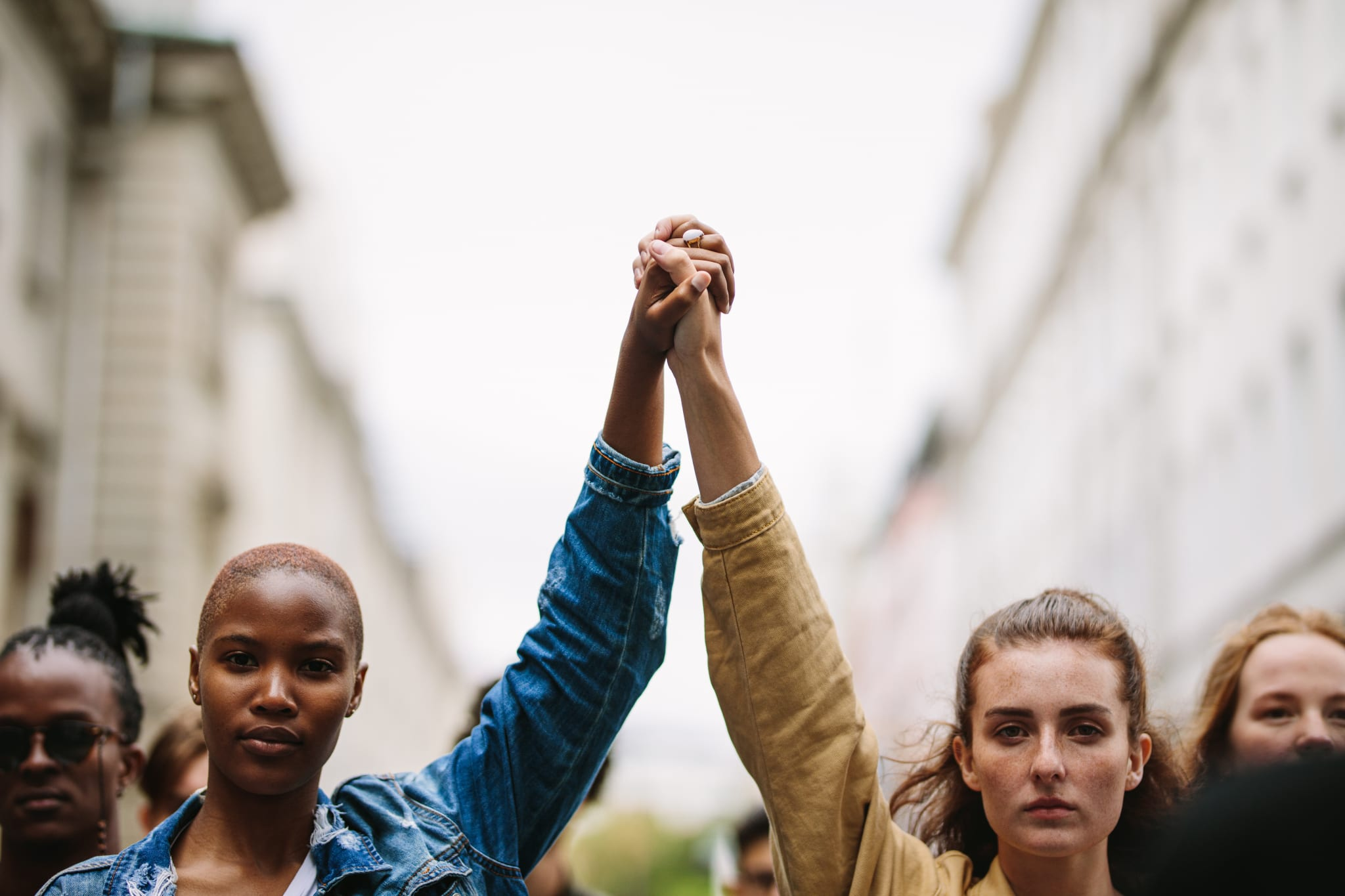 Image of a black woman holding hands with a white woman with their arms raised in the air.