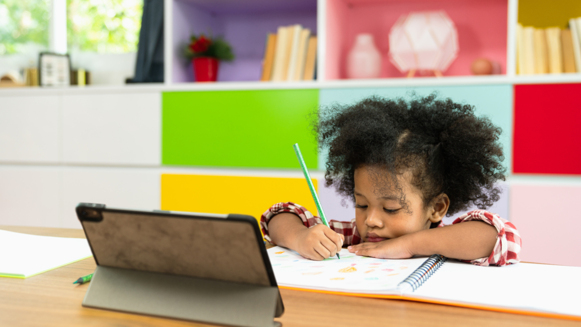 Image of a little girl sitting down in front of a ipad coloring a picture.