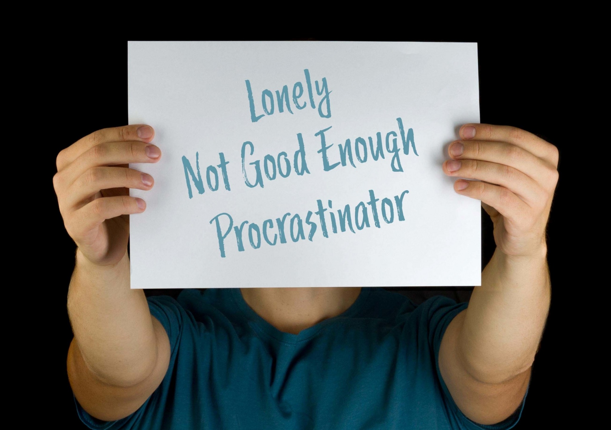"""Stock Photo of a Held Out Poster Reading """"Lonely / Not Good Enough / Procrastinator"""