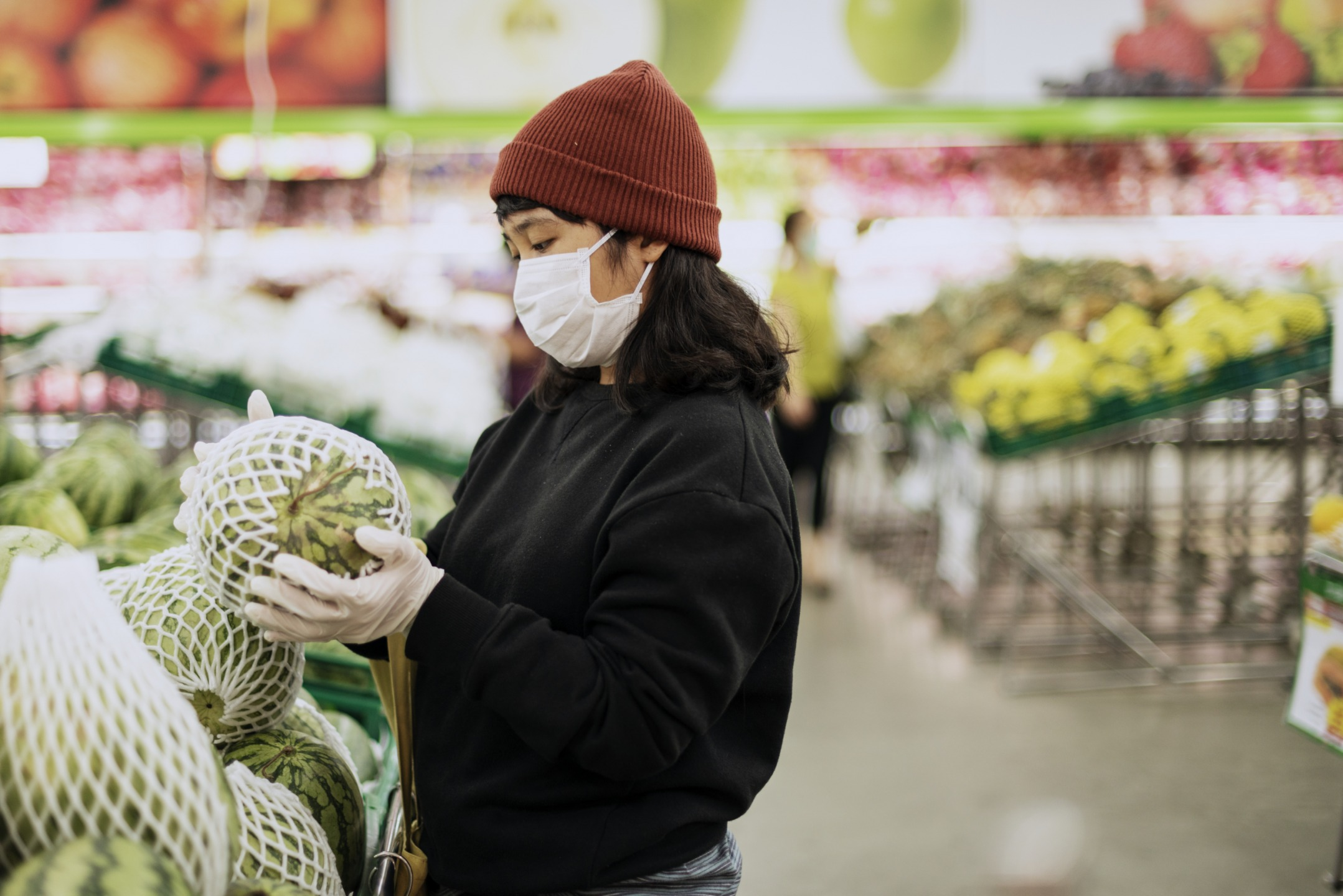 Image of women at a market with a mask on during pandemic